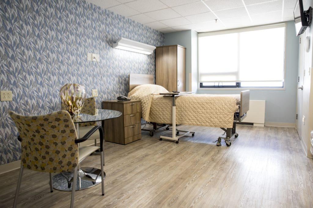 A patient room containing a medical bed, table, chairs, and furniture.
