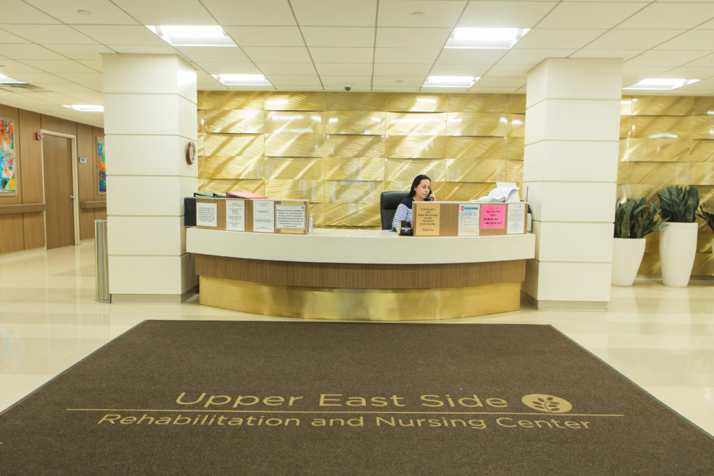 A receptionist is sitting behind the service desk in lobby at Upper East Side Rehab & Nursing Center.