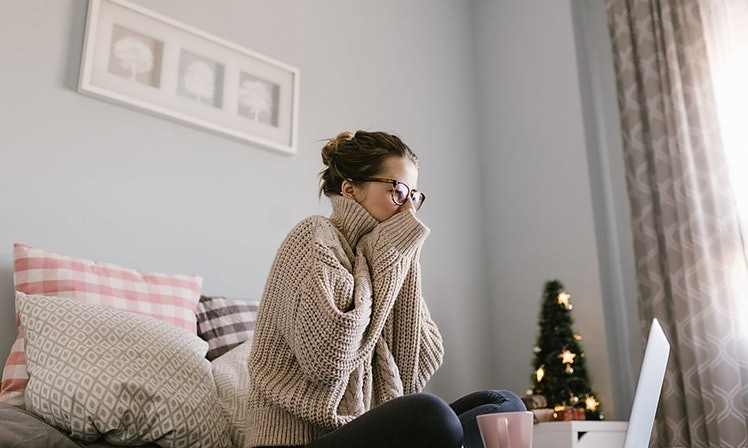 Woman Suffering From Cold Sitting In Bed With Tissue