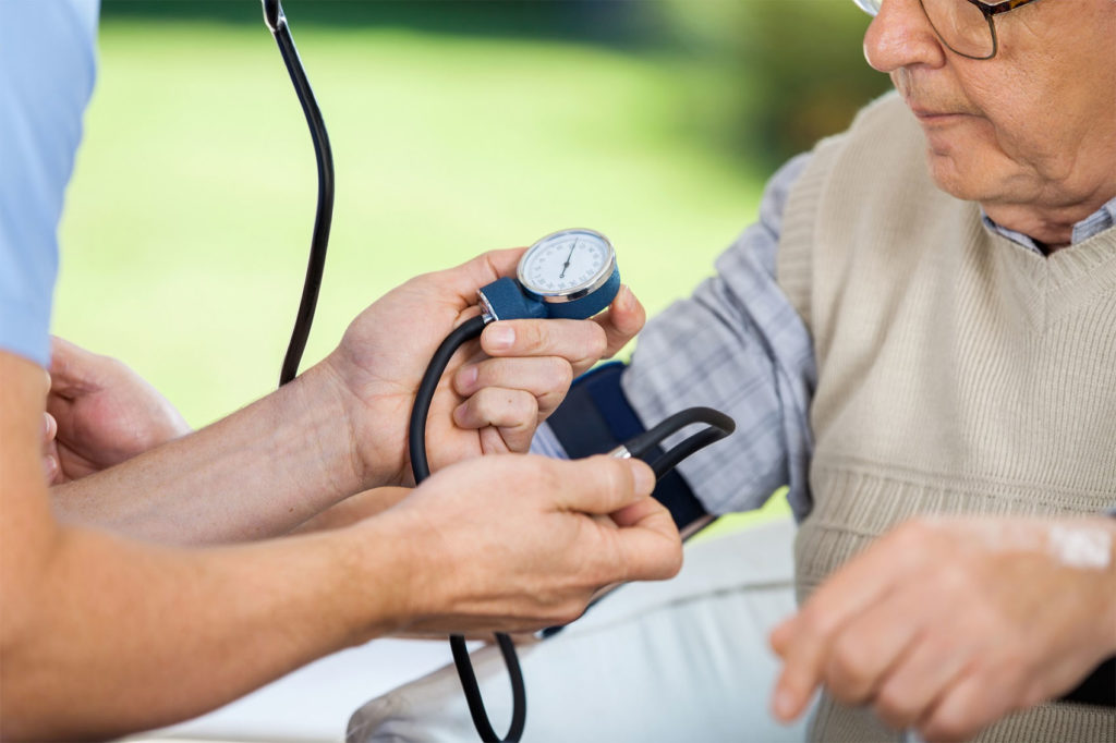 Cropped image of male caretaker measuring blood pressure of elderly man at nursing home