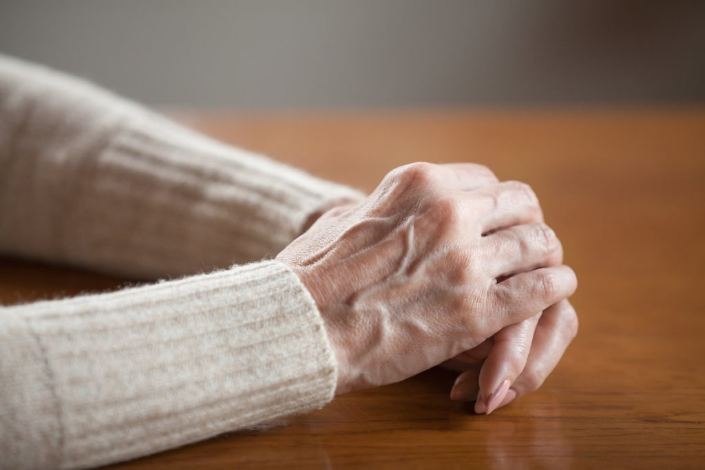 Close up view of mature old female person wrinkled hands with veins on table, middle aged senior elderly woman holding arms folded praying as concept of aging process, healthcare, loneliness or grief