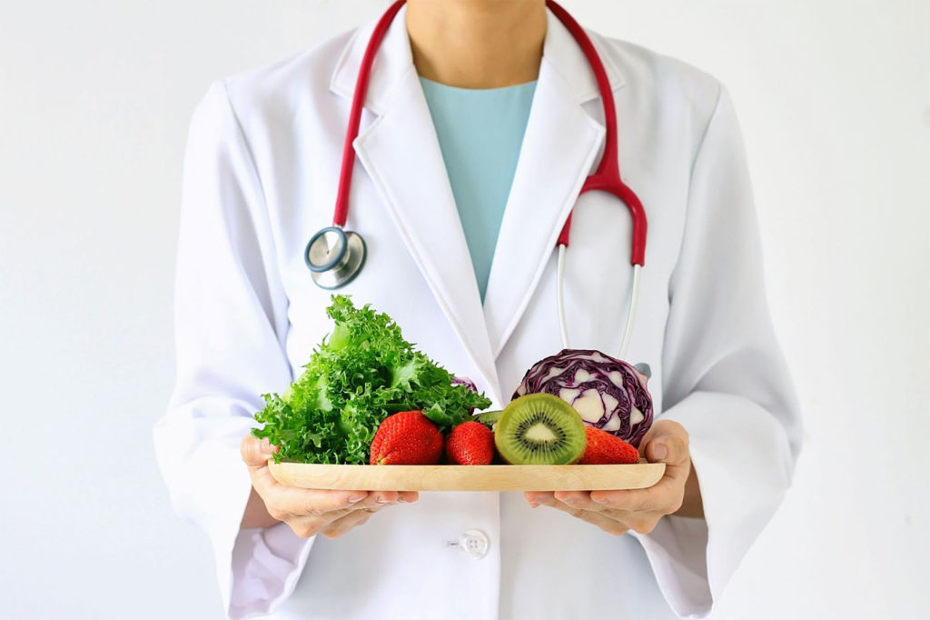 Doctor holding fresh fruit and vegetables