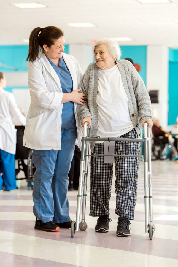 Nurse helping patient with walker