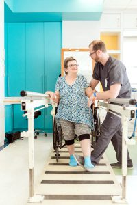 Therapist helping woman walking with parallel bars