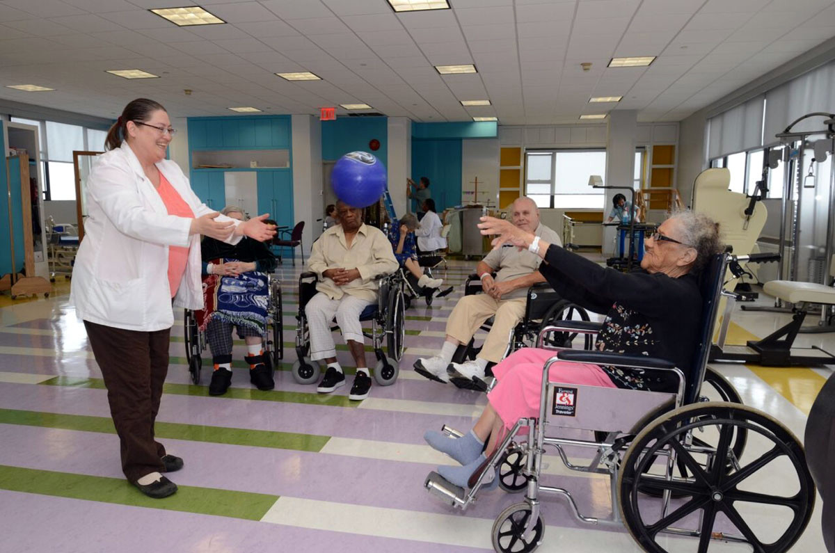 Therapist throws a weighted ball to a woman in a wheelchair in the therapy room